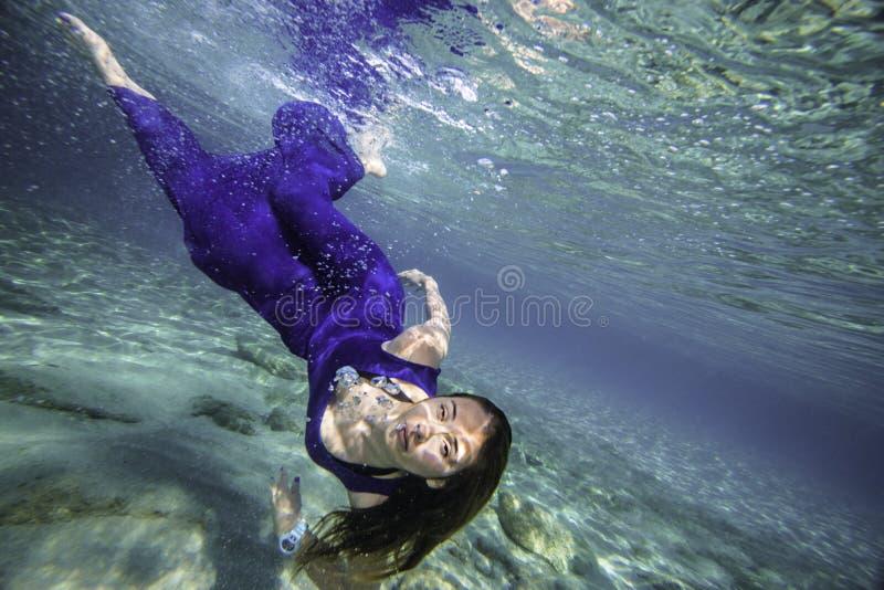 Modelo en el salto azul del vestido foto de archivo