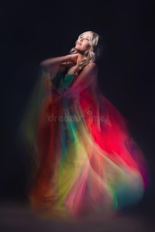Modelo en vestido colorido en fondo negro imagen de archivo