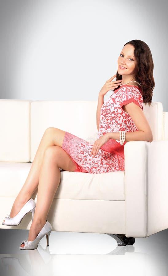Modelo encantador de la mujer que plantea la sentada en una silla fotos de archivo libres de regalías