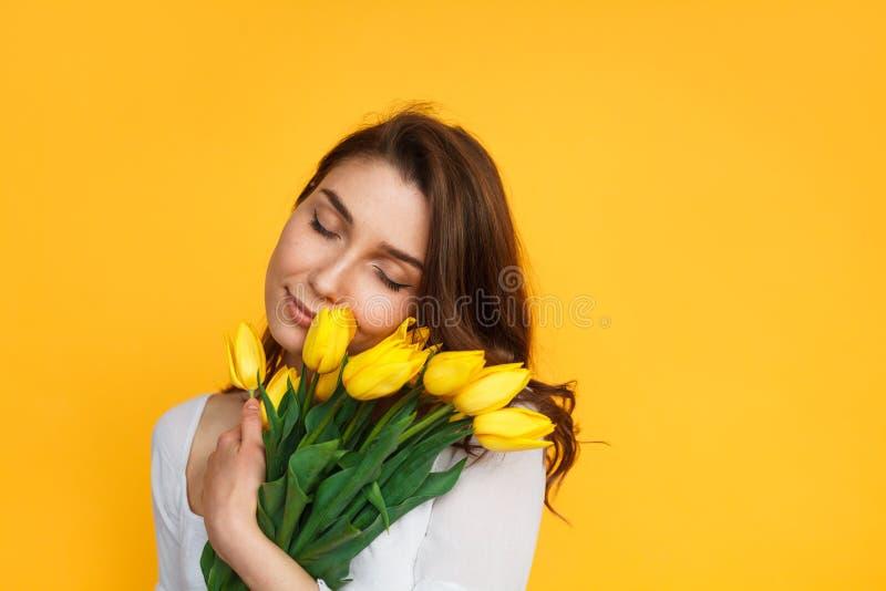 Modelo encantador que goza de tulipanes amarillos fotografía de archivo