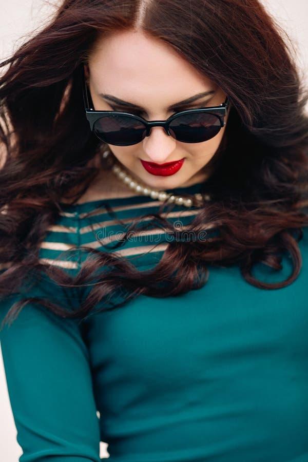 Modelo engraçado nos óculos de sol e em pouco vestido verde, fundo branco Retrato do estilo de vida da forma de feliz novo fotos de stock