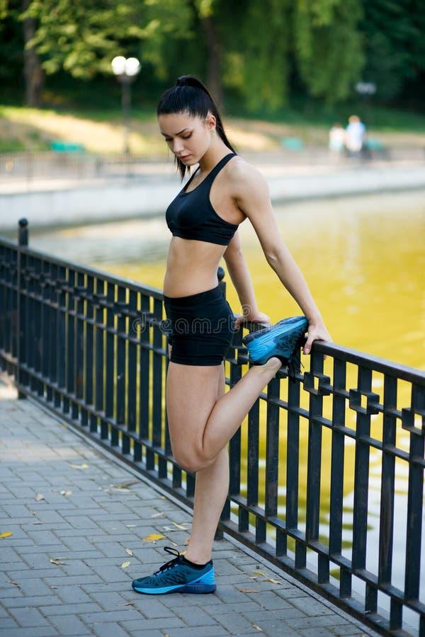 Modelo fêmea apto bonito da menina da aptidão que faz o estiramento que exercita após o exercício fora pelo lago nas horas de ver fotografia de stock royalty free