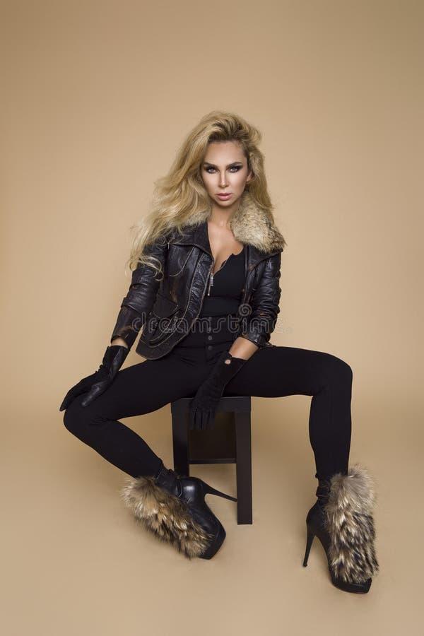 Modelo fêmea bonito em uma roupa, em um casaco de cabedal e em umas botas de outono-inverno em um fundo bege no estúdio Louro den foto de stock