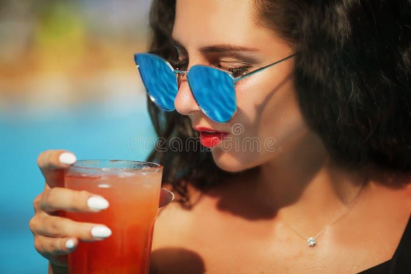 Modelo fêmea caucasiano novo na costa de mar com coctail em t fotografia de stock