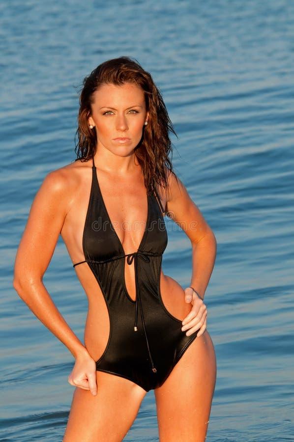 Modelo fêmea da aptidão no oceano no por do sol fotografia de stock royalty free