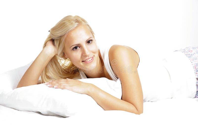 Modelo fêmea do cabelo leve, relaxando na cama imagens de stock