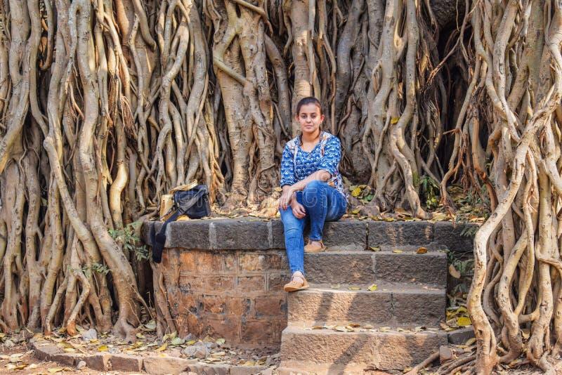 Modelo fêmea feliz que senta-se sob a árvore épico velha enorme e que levanta para uma imagem perfeita fotografia de stock royalty free