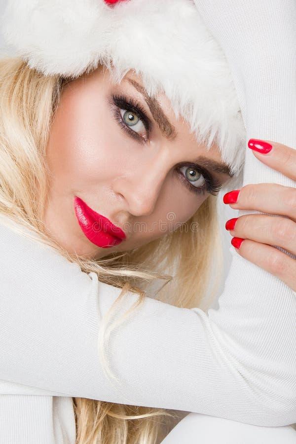 Modelo fêmea louro 'sexy' bonito vestido como Santa Claus em um tampão vermelho fotografia de stock royalty free