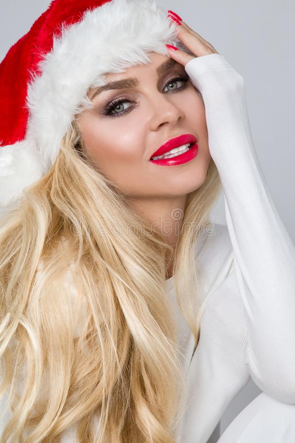 Modelo fêmea louro 'sexy' bonito vestido como Santa Claus em um tampão vermelho imagens de stock royalty free