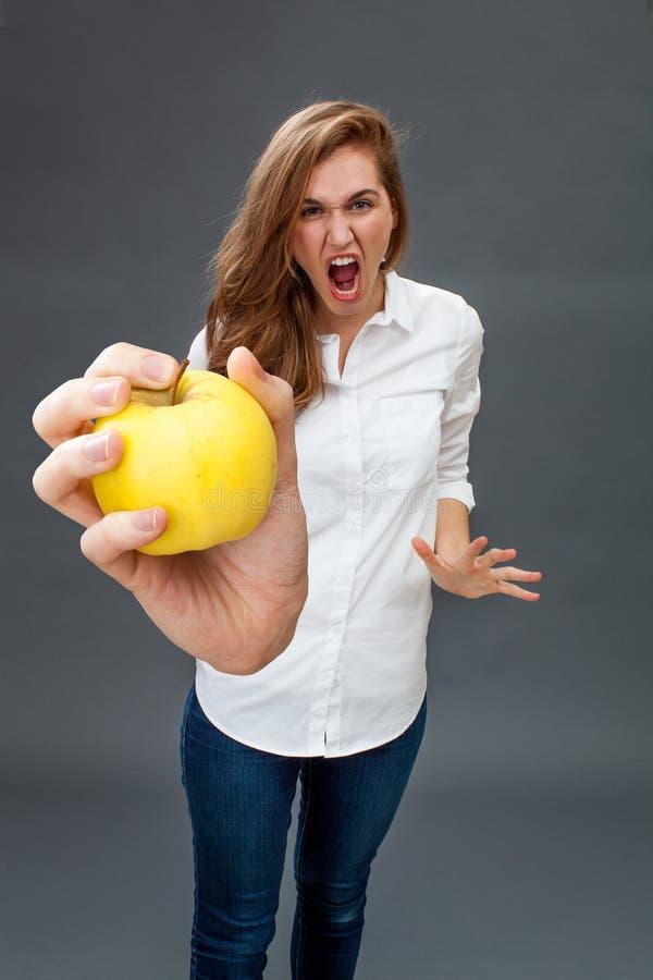 Modelo fêmea novo furioso que grita guardando uma maçã apetitosa fotografia de stock