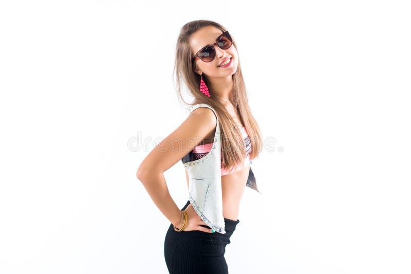Modelo fêmea novo que está lateralmente, dobrando seu corpo, pondo o braço sobre o quadril, óculos de sol vestindo e acessórios b fotos de stock royalty free