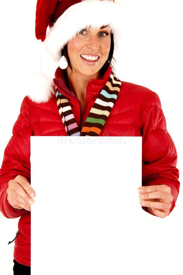 Modelo fêmea que veste um chapéu de Santa e que guarda um sinal vazio foto de stock royalty free