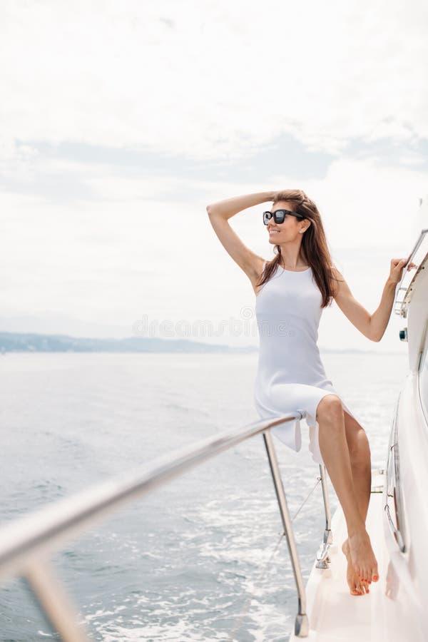 Modelo femenino caucásico en los vidrios que presentan en el barco de navegación de lujo imagen de archivo