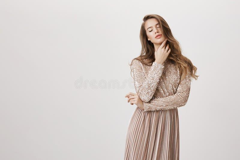 Modelo femenino caucásico femenino sensual que se coloca en el vestido de noche de moda beige, tocando suavemente la piel mientra fotografía de archivo