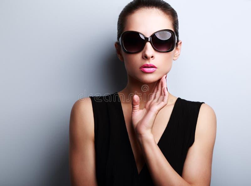 Modelo femenino de la moda atractiva en la presentación de moda de los vidrios de sol foto de archivo libre de regalías