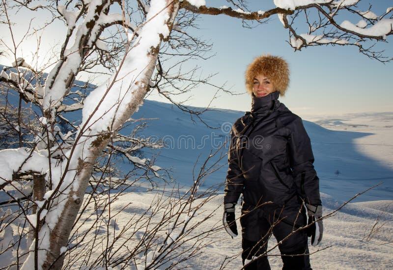 Modelo femenino de risa feliz lindo joven de la mujer que juega con las ramas de árboles nevosas que sonríen de la diversión y de imagen de archivo libre de regalías
