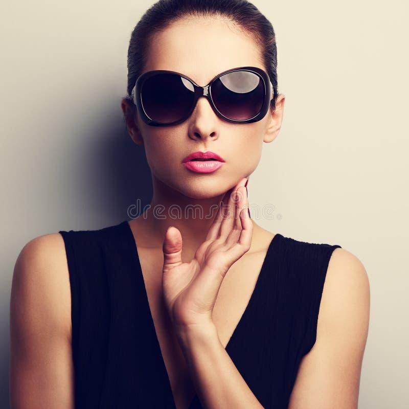 Modelo femenino del encanto atractivo en vidrios de sol de moda con la mano en el fac fotos de archivo libres de regalías