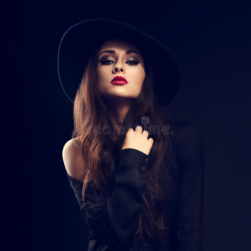 Modelo femenino del encanto atractivo que presenta en camisa negra y sombrero elegante fotos de archivo libres de regalías