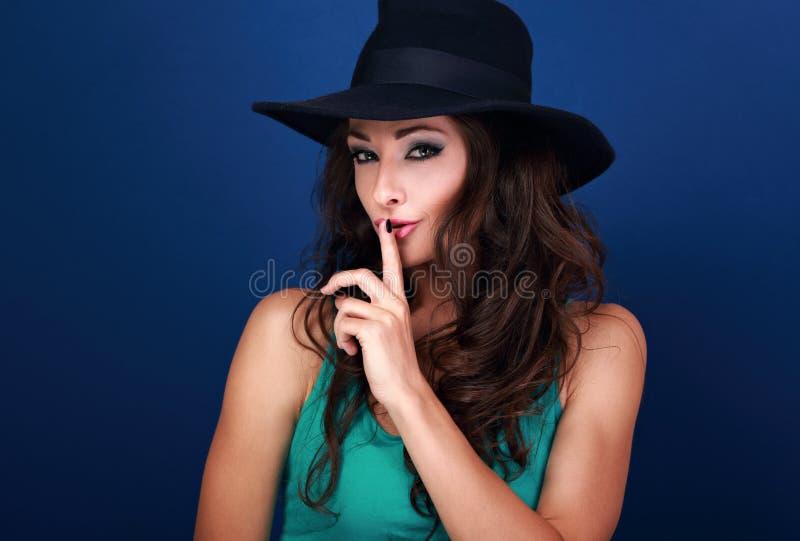 Modelo femenino del maquillaje hermoso en el sombrero que muestra la muestra secreta en azul imagenes de archivo