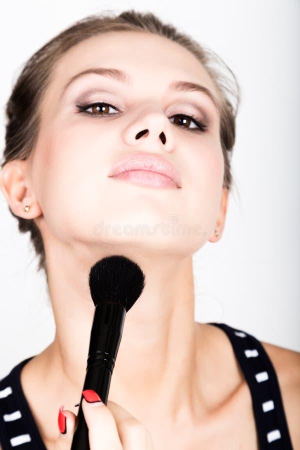 Modelo femenino del primer que aplica maquillaje en su cara Mujer joven hermosa que aplica la fundación en su cara con un compone fotografía de archivo libre de regalías