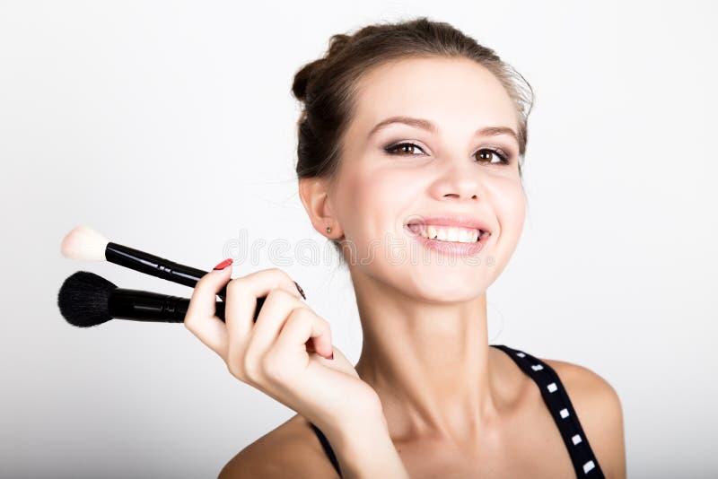 Modelo femenino del primer que aplica maquillaje en su cara Mujer joven hermosa que aplica la fundación en su cara con un compone imagen de archivo libre de regalías