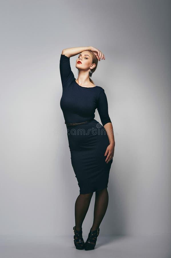 Modelo femenino del tamaño extra grande que presenta en vestido foto de archivo