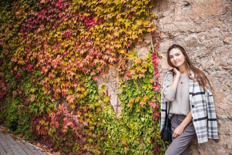 Modelo femenino en equipo de moda en el fondo de la pared del steet fotos de archivo