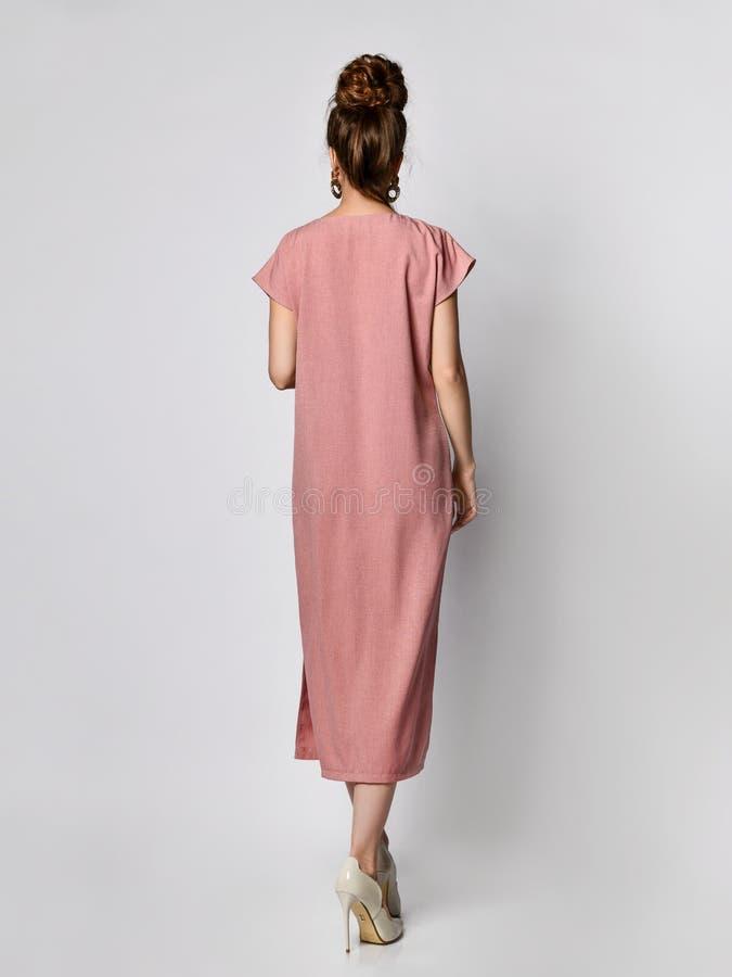 Modelo femenino en un pálido de seda en el vestido largo s del verano casual del diseño del rosa que mira la cámara en crecimient fotos de archivo libres de regalías
