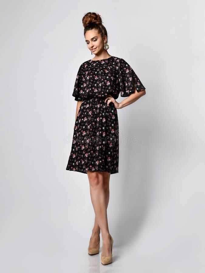 Modelo femenino en un vestido corto de seda que mira la cámara en crecimiento completo La muchacha linda en ropa romántica va una fotografía de archivo libre de regalías
