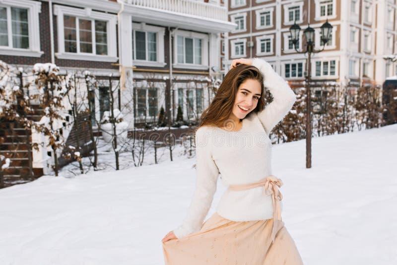 Modelo femenino encantador en suéter y el baile rosado de la falda en la yarda por mañana del invierno Foto al aire libre de la m fotos de archivo libres de regalías