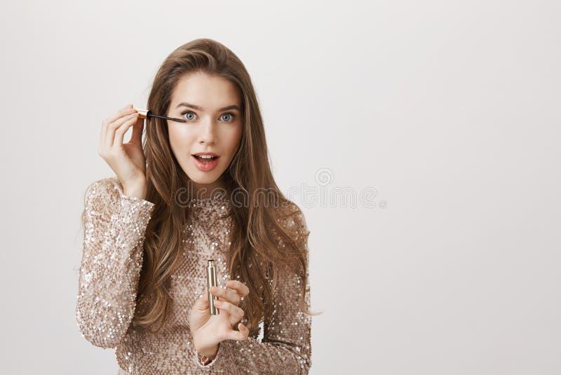 Modelo femenino europeo atractivo alegre que se coloca delante del espejo en vestido de noche y que pone en el rimel con enfocado imagen de archivo