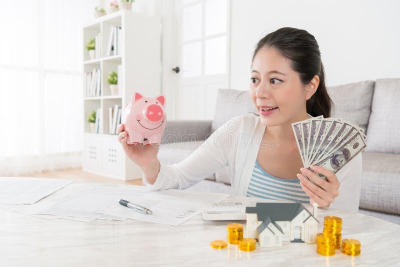 Modelo femenino feliz sonriente que sostiene la hucha rosada fotografía de archivo