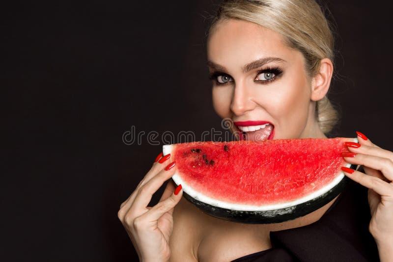 Modelo femenino hermoso con la cara perfecta y el cuidado de piel liso, sosteniendo y comiendo la fruta de la sandía foto de archivo