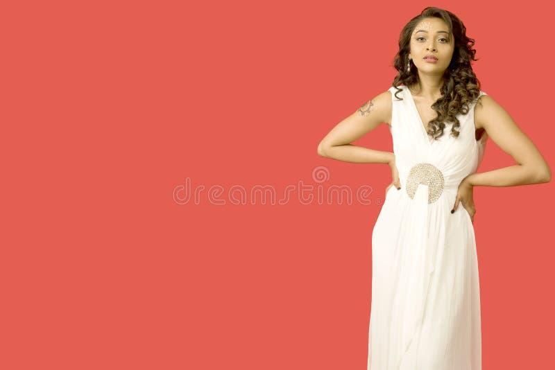 Modelo femenino hermoso en un vestido blanco flowy delante de un fondo rojo sólido imágenes de archivo libres de regalías