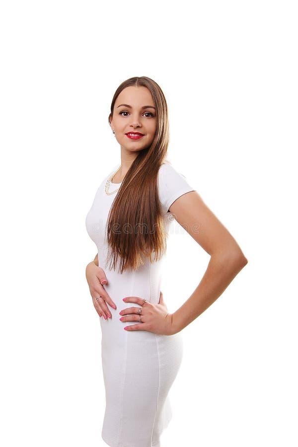 Modelo femenino hermoso joven en el vestido blanco en fondo gris foto de archivo