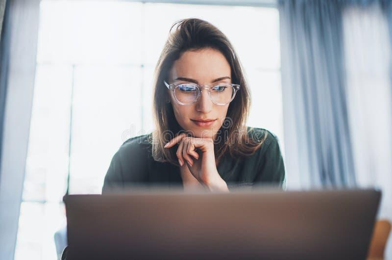 Modelo femenino hermoso joven que se sienta en la butaca c?moda y que usa el ordenador port?til Proceso de trabajo en coworking fotos de archivo