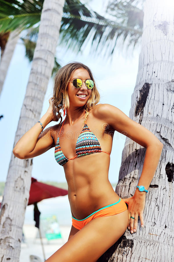 Modelo femenino hermoso que presenta en una playa cerca de las palmas imagen de archivo libre de regalías