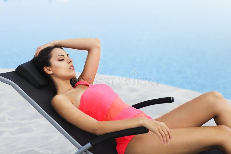Modelo femenino hermoso que presenta por la piscina al aire libre fotografía de archivo