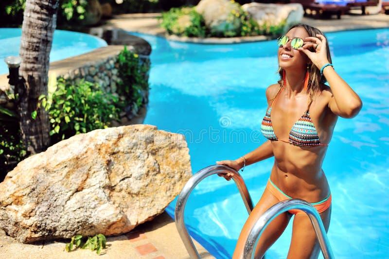 Modelo femenino hermoso que presenta por la piscina, retrato al aire libre imagen de archivo