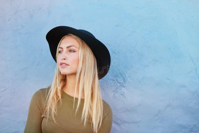 Modelo femenino joven atractivo con el sombrero que mira lejos foto de archivo libre de regalías