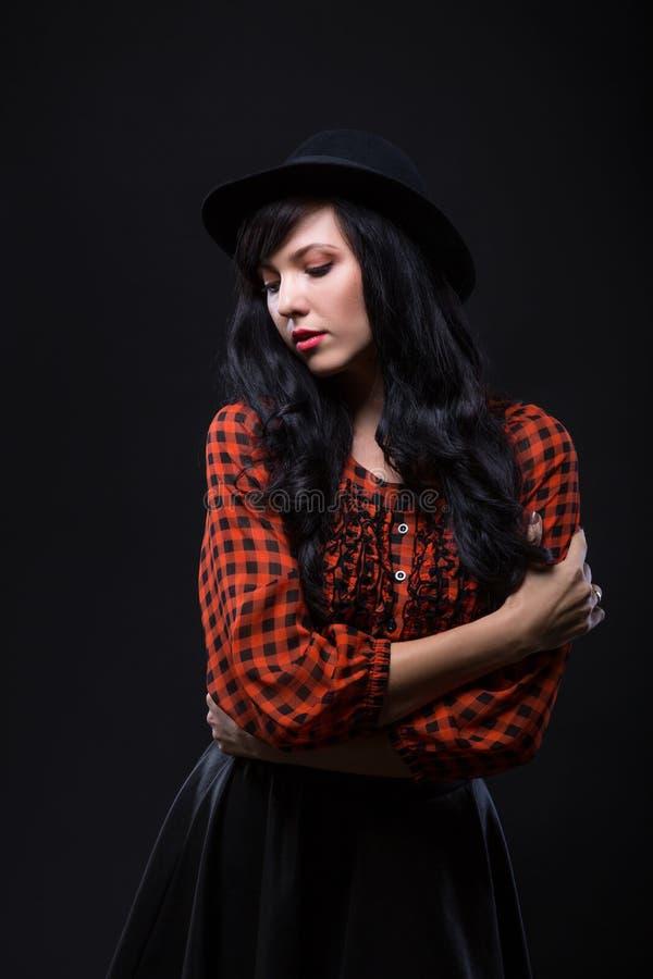 Modelo femenino moreno de la emoción que presenta en sombrero negro con el lápiz labial brillante rojo en fondo negro retrato de  fotografía de archivo libre de regalías