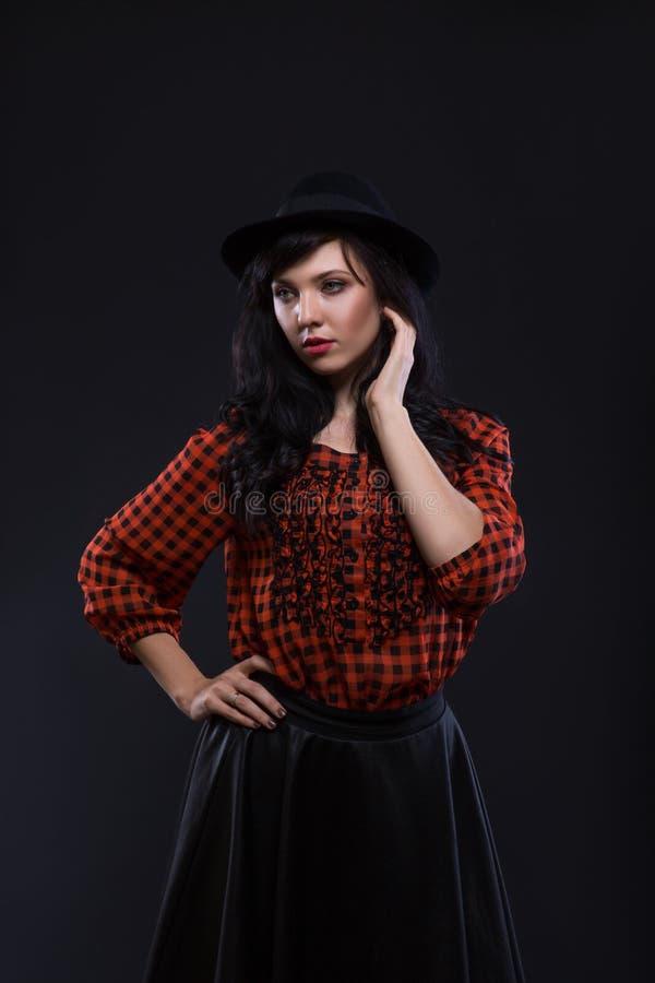 Modelo femenino moreno de la emoción que presenta en sombrero negro con el lápiz labial brillante rojo en fondo negro retrato de  fotos de archivo