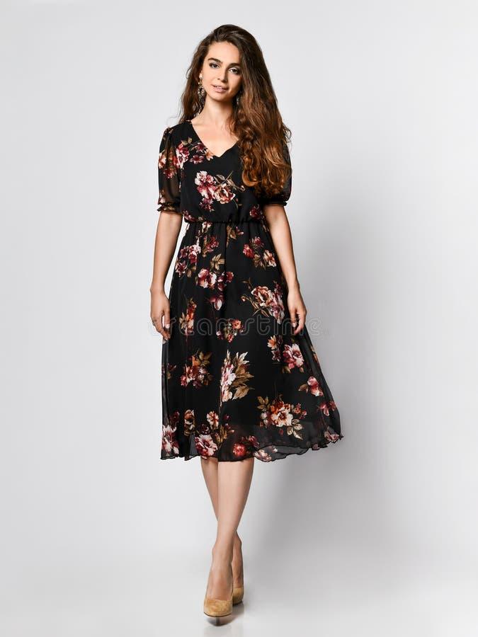 Modelo femenino rizado en un vestido negro de seda que mira la cámara en crecimiento completo La muchacha linda en ropa romántica imágenes de archivo libres de regalías
