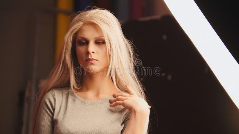 Modelo femenino rubio joven en estudio de la foto - funcionamiento del fotógrafo foto de archivo libre de regalías