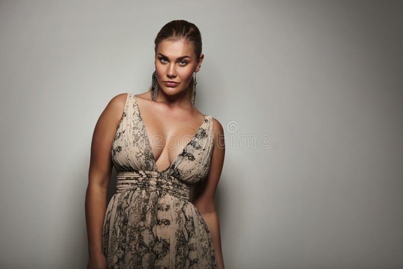 Modelo femenino voluptuoso que presenta un vestido hermoso imágenes de archivo libres de regalías