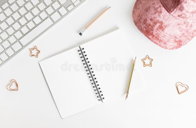 Modelo feminino colocado plano do bloco de desenho da vista superior: lápis, clipes de papel, chapéu cor-de-rosa e teclado no fun fotografia de stock