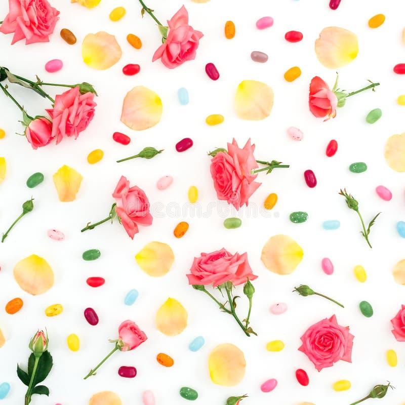 Modelo hecho de las flores y de los pétalos de las rosas con el caramelo de azúcar brillante en el fondo blanco Endecha plana, vi fotos de archivo