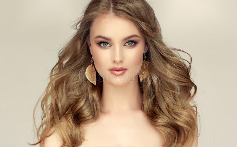 Modelo hermoso con largo, denso, libremente poniendo el peinado y el maquillaje aseado imagen de archivo