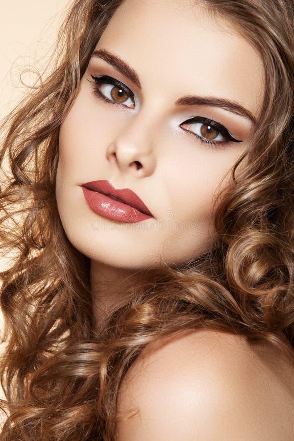 Modelo hermoso con maquillaje, pelo rizado largo de la mujer fotografía de archivo