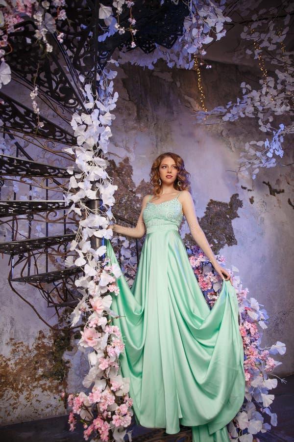 Modelo hermoso de la mujer en un vestido menta-coloreado en un fondo florecido de la primavera Muchacha de la belleza con un maqu fotografía de archivo libre de regalías